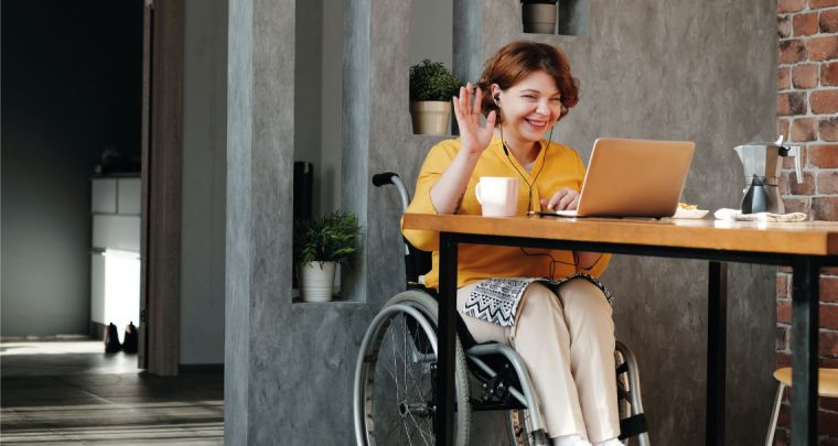 Photo of a lady in a wheel chair having a meeting over video conferencing using a laptop
