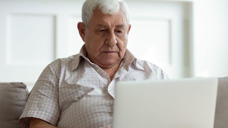 An older man looking on his laptop