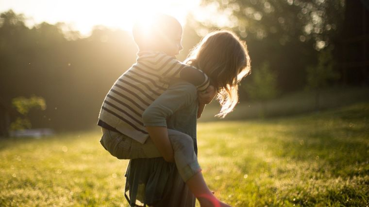 Boy and girl playing piggyback rides.