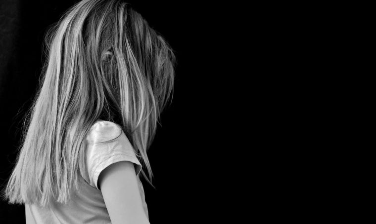 A young girl facing away in black and white.