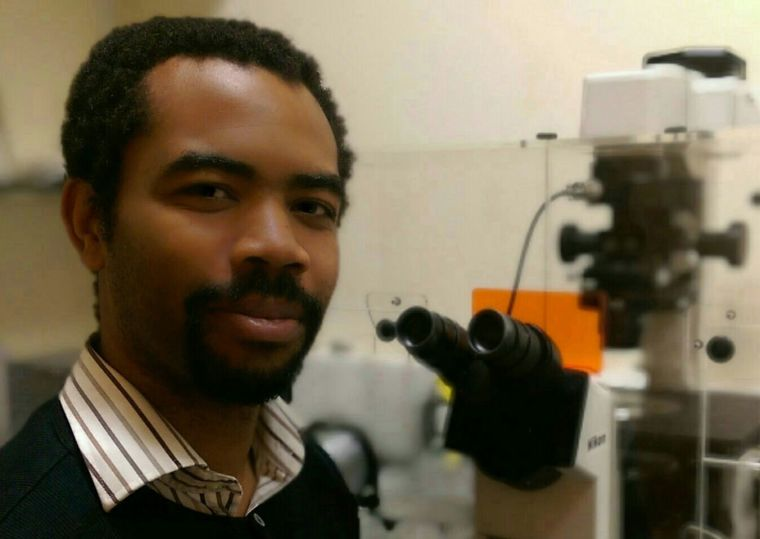 Dayne photographed in the lab next to a microscope