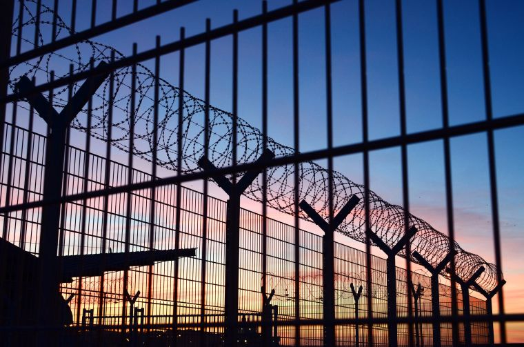 Border fencing and barbed wire at Dieppe, France, at sunset
