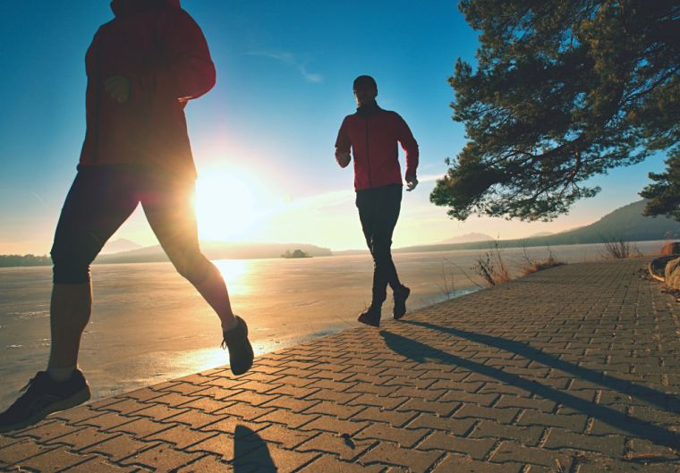 Image of two people running along the waterfront as the sunrises.
