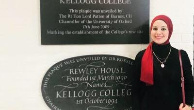 Ranin Soliman standing next to plaques at Kellogg College, Oxford