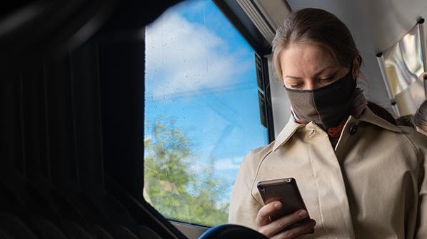 Image of woman on a train using a mobile phone whilst wearing a face mask