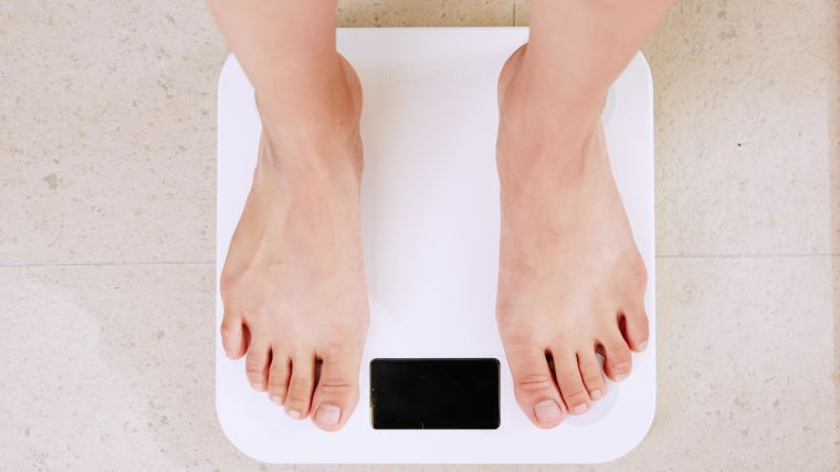 A photo looking down of a person's feet standing on a set of weighing scales
