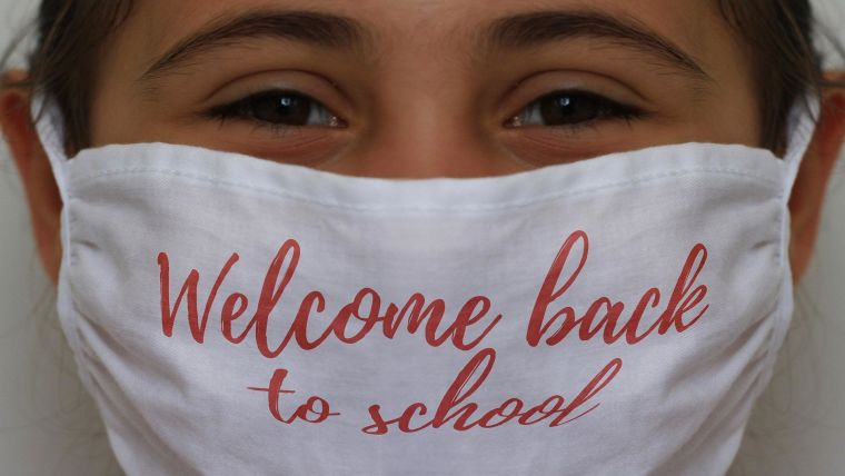 "A girl wearing a mask with ""welcome back to school"" written on it."