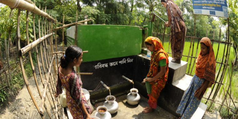 Local women collecting water in large jars.