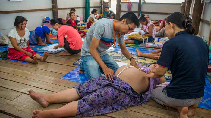 Health care workers checking a pregnant woman