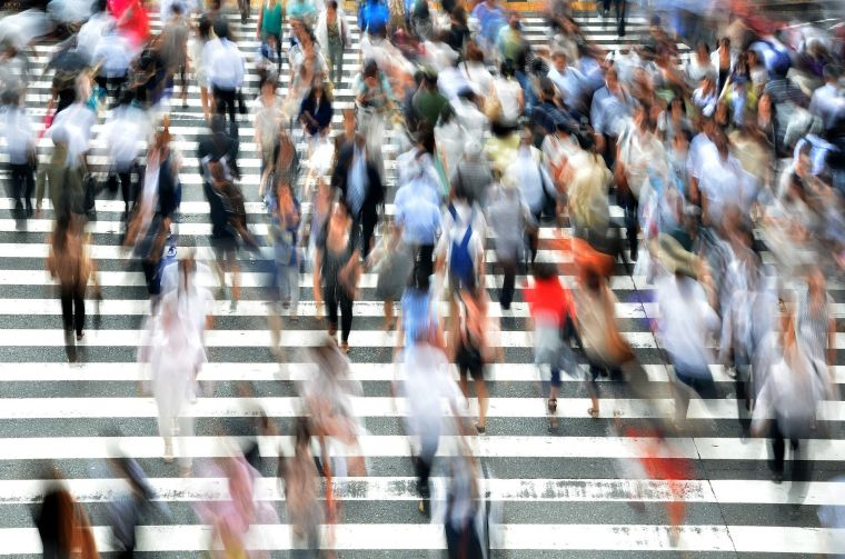 Blurred image of a large group of pedestrians on a road crossing