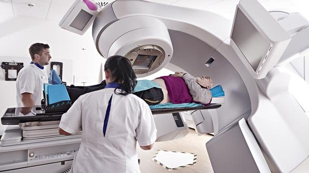 Radiologist treating cancer patient with radiotherapy