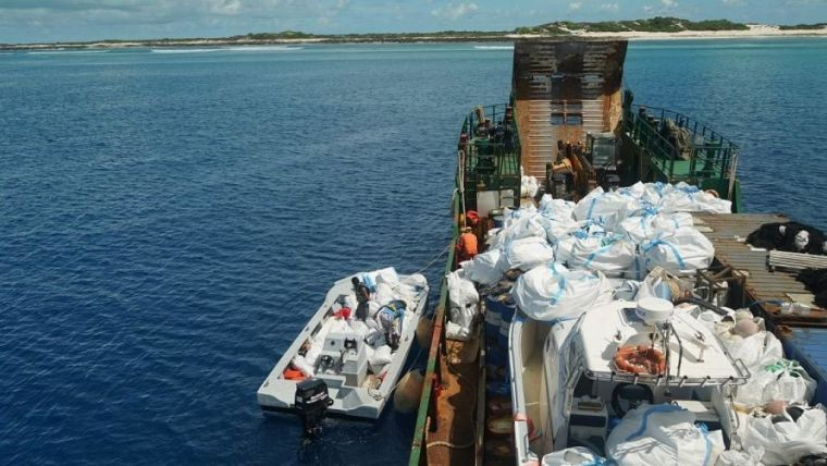 Boat collecting waste from Aldabra