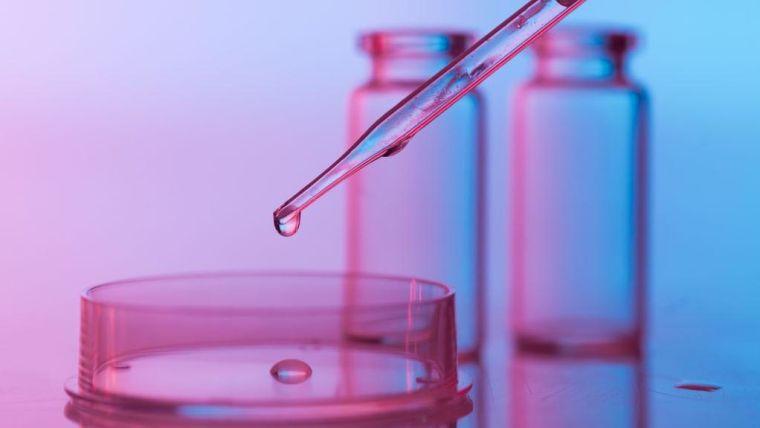 pipette dropping a transparent liquid in a petri dish