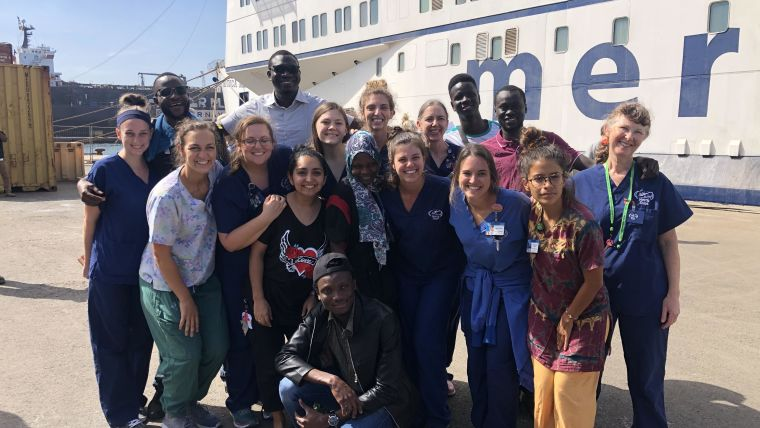 Gabrielle Dent with colleagues standing in front of the African Mercy ship.