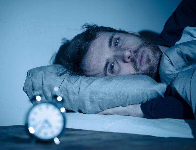 A man with tired eyes laying down in bed with an alarm clock blurred in the image.