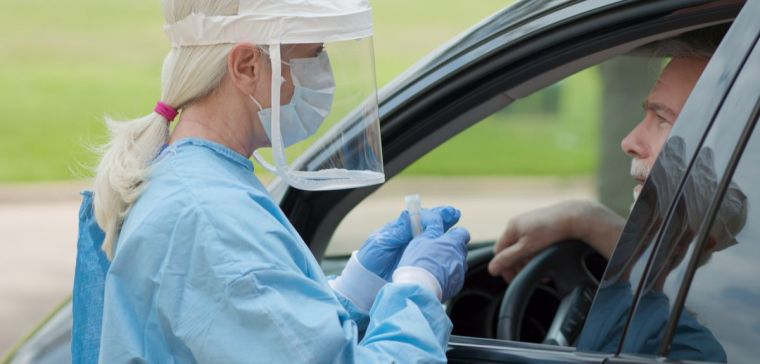Healthcare worker wearing full PPE collects a sample at a coronavirus mobile testing unit