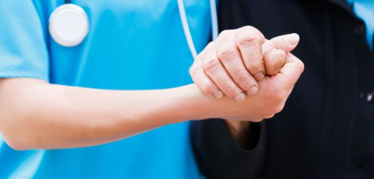 Nurse or doctor holding elderly patient's hand with care