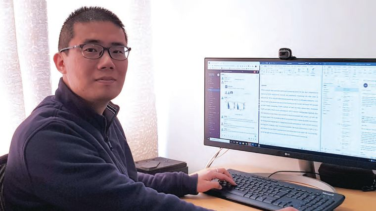 A photo of Chunxiao Song working in front of a computer