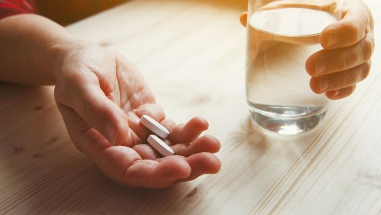 A senior woman's hand holding medication with a glass of water.