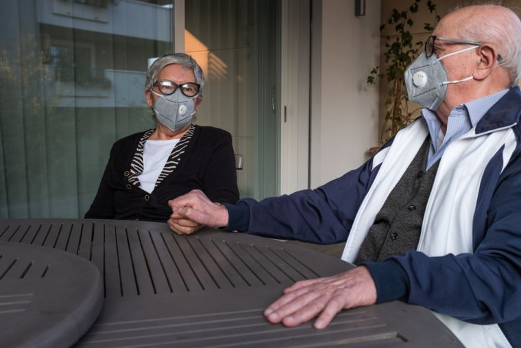 Older couple wearing masks and holding hands around table