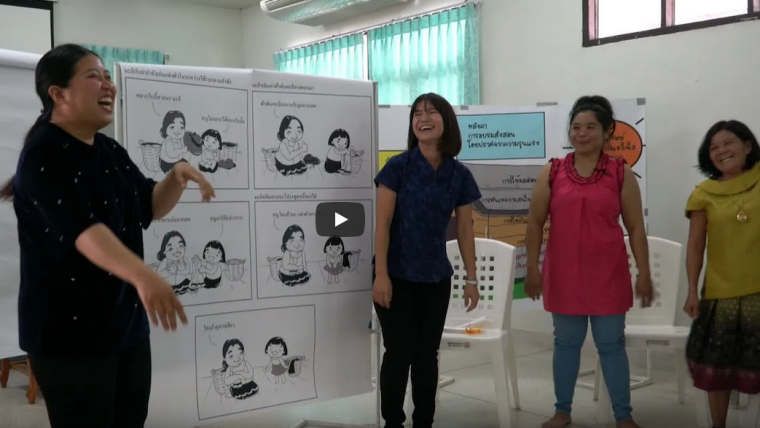 Thai participants to a workshop about the project Parenting for Life discuss in front of illustrations of parent-child typical behaviour