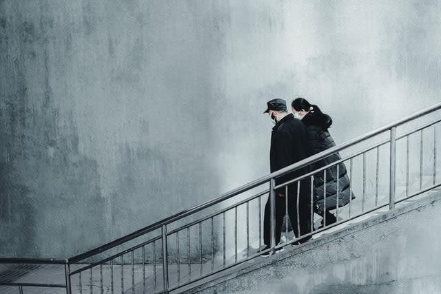 A couple walking downstairs wearing masks during the coronavirus pandemic