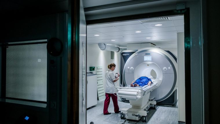 Person going into MRI scanner with radiographer standing by