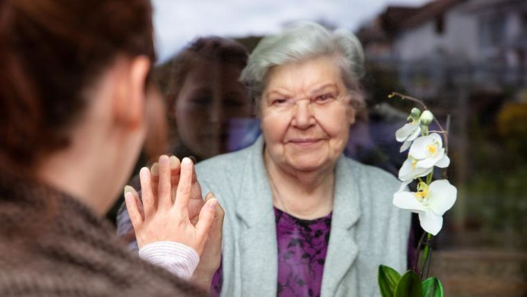 An older lady indoors with her hand up to the glass. A younger person makes a heart sign at her.