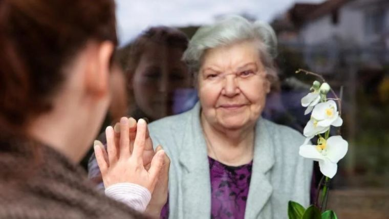 Family members seeing each other through window pane