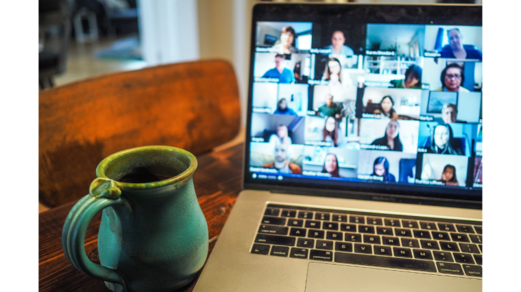 Open laptop on a table with a virtual meeting taking place