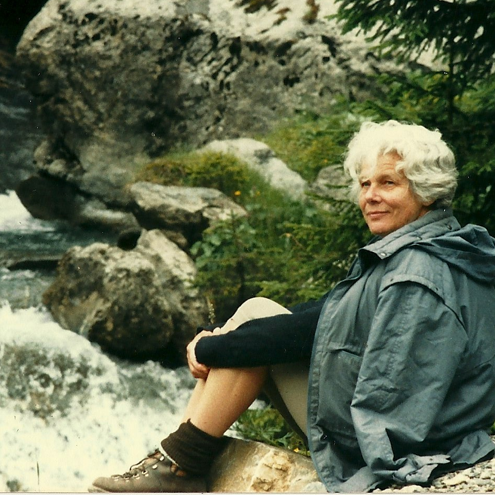 Modern colour photograph of Marianne Fillenz outside by a waterfall.