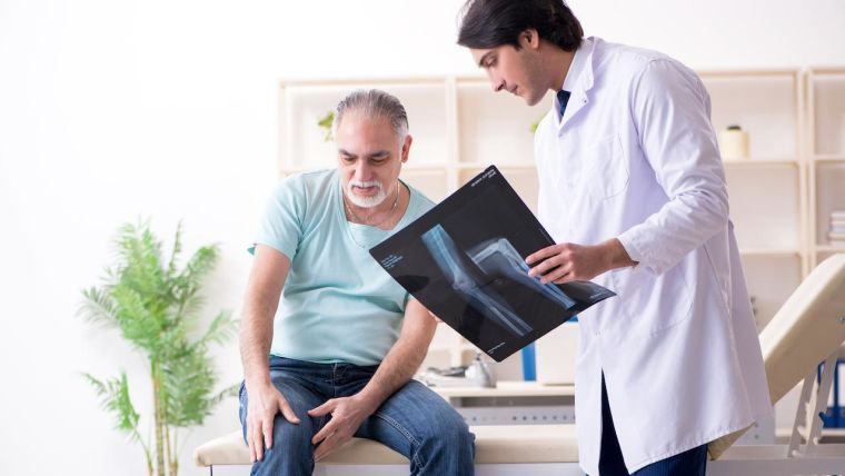 A doctor treats a patient with knee osteoarthritis