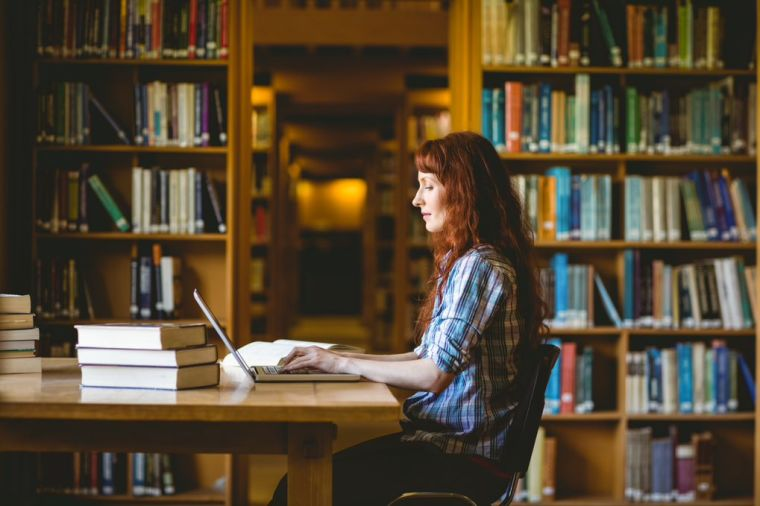 Student using laptop at desk in a library