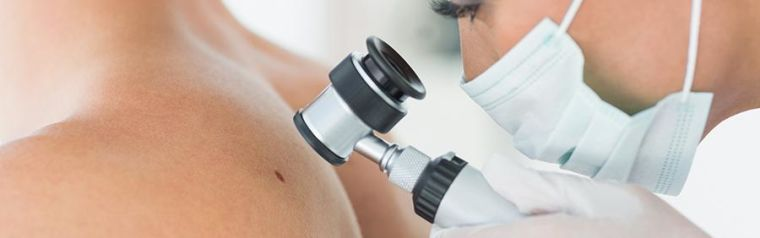 Doctor looking at a skin blemish on a patient using doctors tools