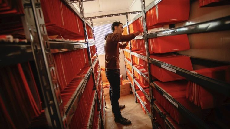 A UNHCR staff member works amongst rows of files