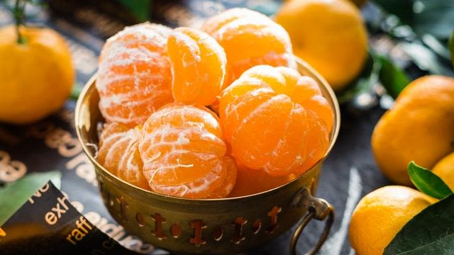 Bowl of peeled oranges with whole oranges scattered around.