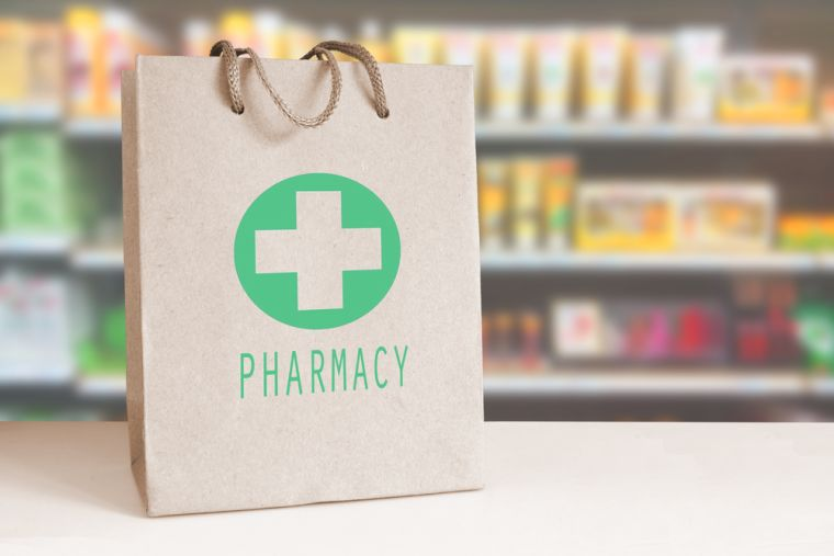 A bag with the word 'pharmacy' on a counter in a shop.