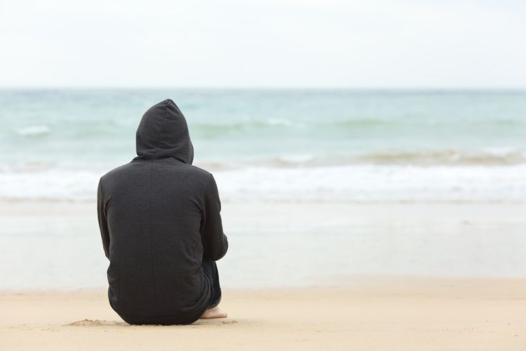 A boy in a hoodie sitting on a beach looking out to sea