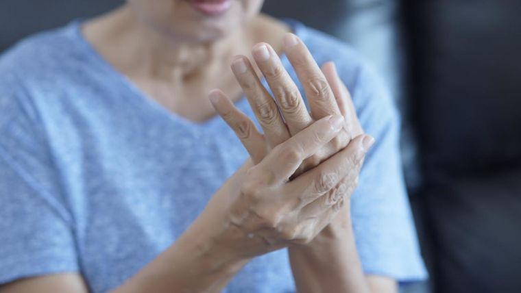 A woman suffering with rheumatoid arthritis rubs her hands