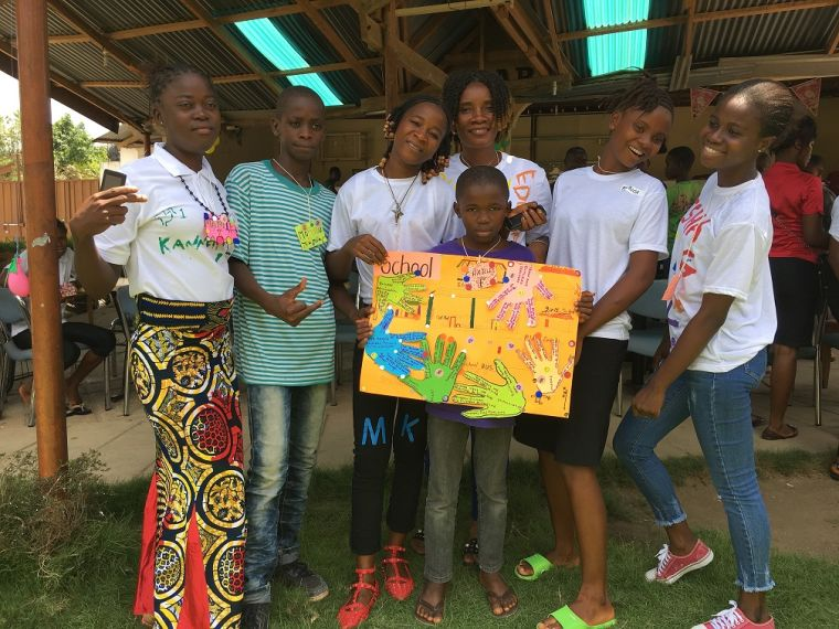 Image shows group of African people, some adults, children and teenagers, smiling and holding up a colourful piece of artwork one of the children has created.