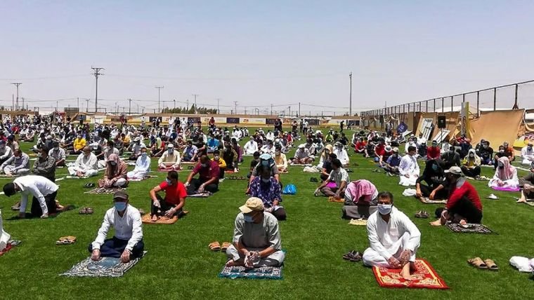 Syrian refugees attend Friday prayers outside, socially-distanced, following COVID-19 restrictions at Za'atari refugee camp