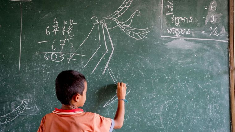 A child writes something on a blackboard