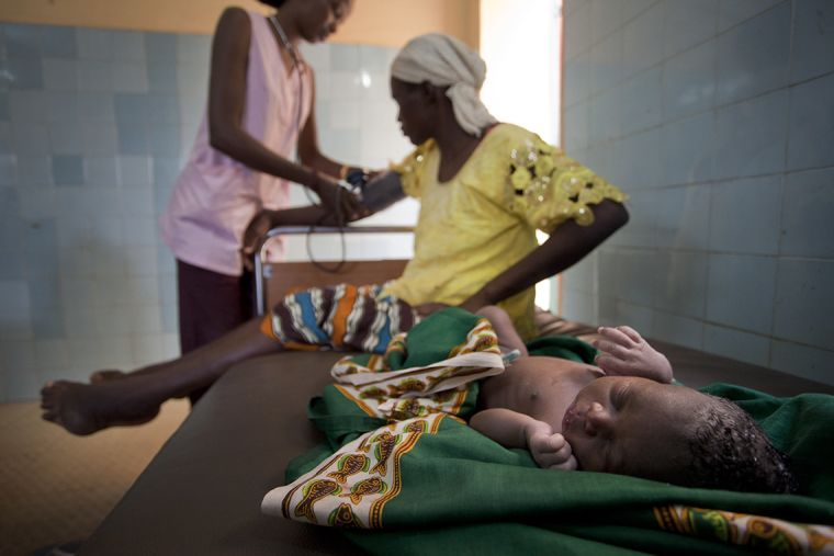 Mother and child on a healthcare bed. The mother is being checked by a health care worker