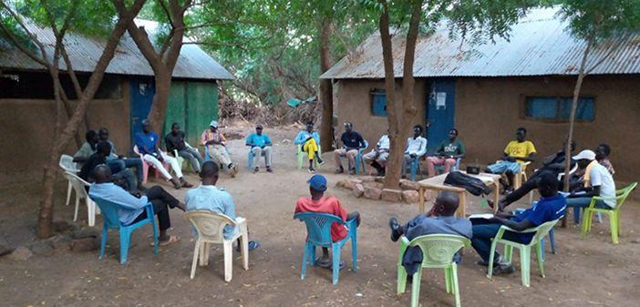Men sitting in a circle to discuss a dispute outside at Kakuma camp