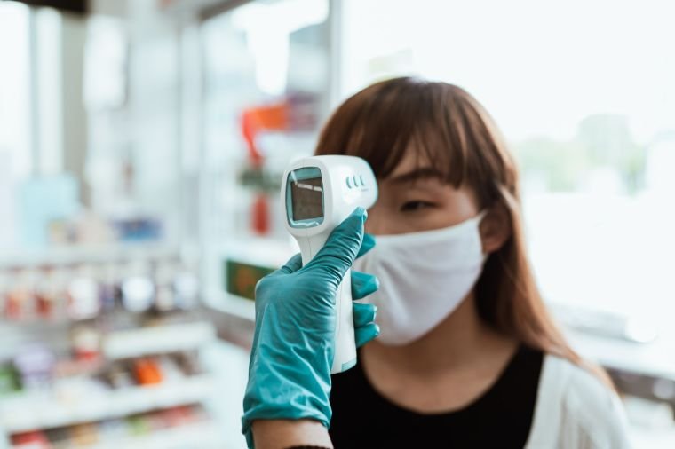 A photograph of aa woman having her temperature measured using an infrared thermometer.