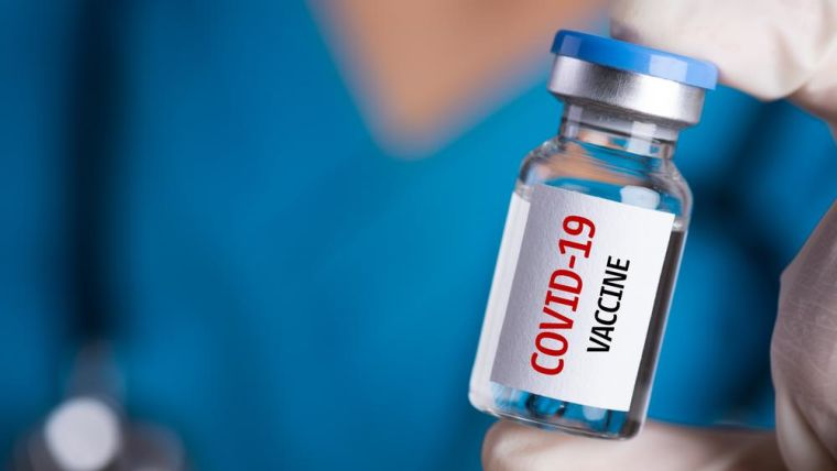 A bottle of COVID-19 vaccine held by a health professional