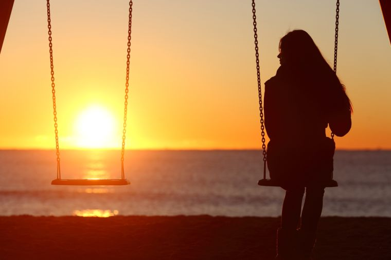 Woman sat on swing seat with beach sunset in background
