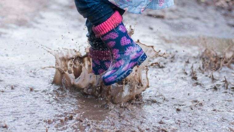 Young child wearing wellington boots splashes in a puddle