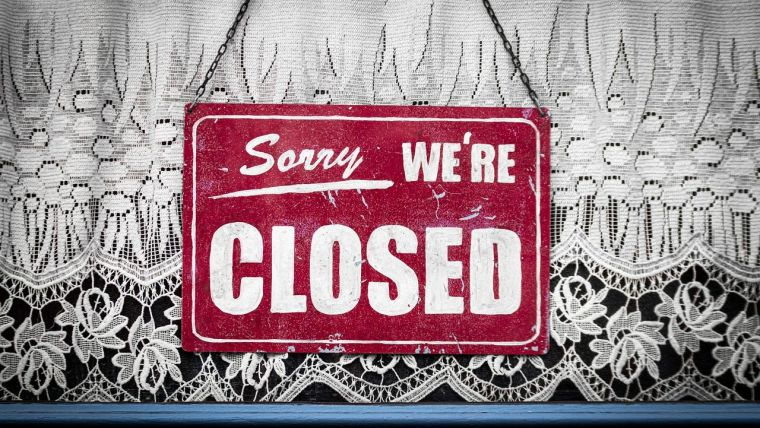 'Sorry, we're closed' sign in a window.