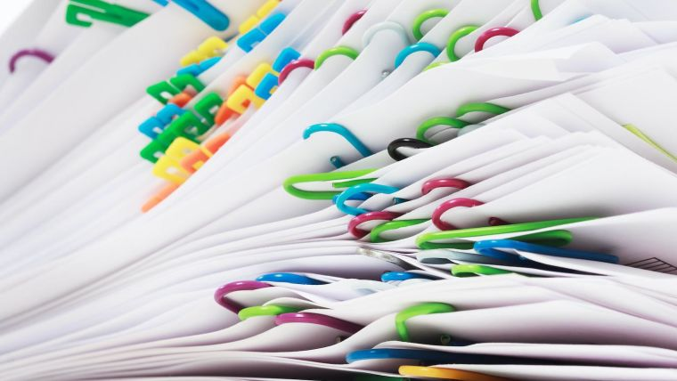 Pile of papers with bright paperclips
